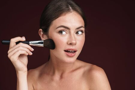 Image of young half-naked woman looking aside and using makeup brush isolated over dark red background