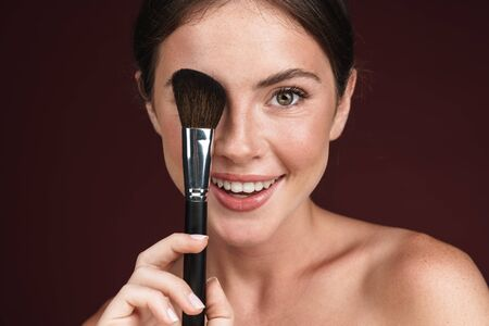 Image of cheerful half-naked woman looking at camera and using makeup brush isolated over dark red background