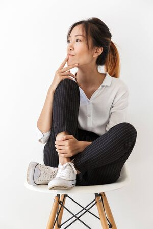 Attractive pensive young asian woman sitting on a chair isolated over white background, looking away
