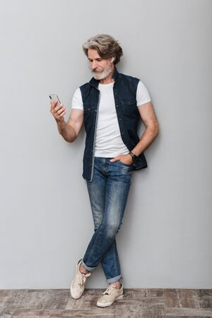 Full length portrait of a handsome smiling stylish mature man wearing a vest standing over gray background, using mobile phone