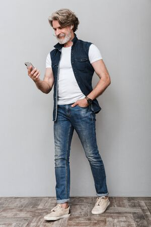 Full length portrait of a handsome smiling stylish mature man wearing a vest walking over gray background, using mobile phone Imagens