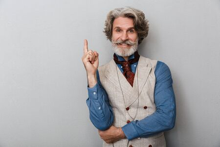 Photo of a bearded emotional handsome senior man with grey hair isolated over grey wall background have an idea.