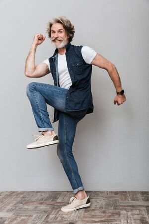 Full length portrait of an excited handsome stylish mature man wearing a vest standing on one leg over gray background Banco de Imagens