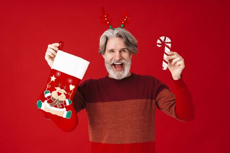 Portrait of bearded old man in sweater holding candy cane and Christmas gift sock isolated over red background Banco de Imagens