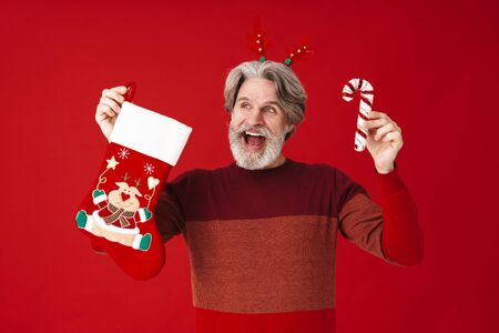 Portrait of bearded old man in sweater holding cane candy and Christmas gift sock isolated over red background