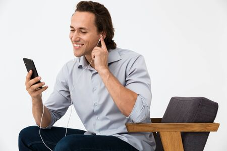 Image of caucasian businessman listening to music with smartphone and earphones on armchair isolated over white background