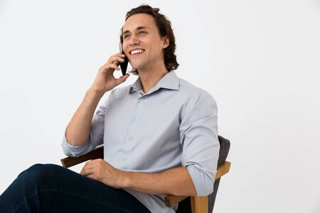 Image of cheerful businessman in office shirt talking on smartphone while sitting in armchair isolated over white background