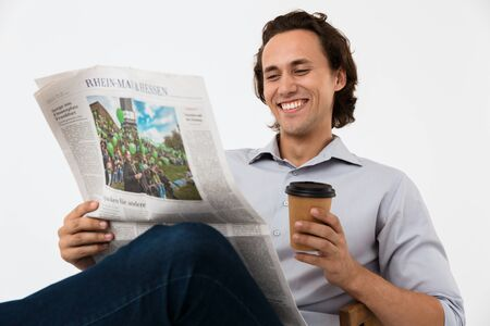 Image of caucasian businessman in office shirt drinking coffee and reading newspaper in armchair isolated over white background Stock Photo