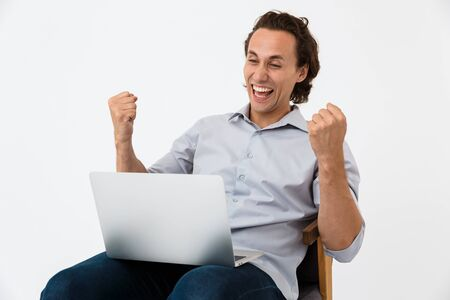 Image of excited businessman in office shirt rejoicing while sitting on armchair with laptop computer isolated over white background