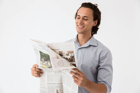 Image closeup of young businessman in office shirt smiling and reading newspaper isolated over white background