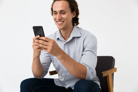 Image of caucasian businessman in office shirt holding smartphone while sitting on armchair isolated over white background