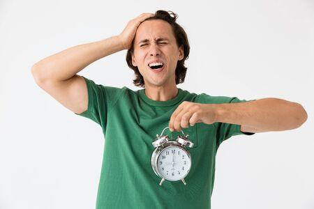 Image of uptight brunette man wearing basic t-shirt screaming and holding alarm clock isolated over white background