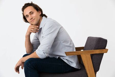 Image of elegant businessman in office shirt looking at camera while sitting on armchair isolated over white background Stock Photo