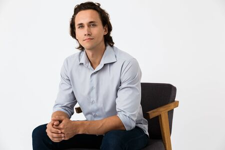 Image of positive businessman in office shirt looking at camera while sitting on armchair isolated over white background Stock Photo