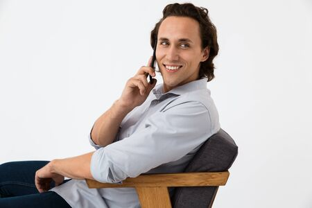 Image of positive businessman in office shirt talking on smartphone while sitting in armchair isolated over white background Stock Photo