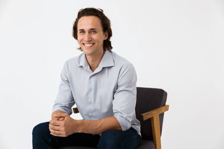 Image of handsome businessman in office shirt looking at camera while sitting on armchair isolated over white background Stock Photo