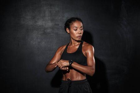 Atractiva joven deportista africana muscular que se encuentran aisladas sobre fondo negro, comprobando el tiempo Foto de archivo