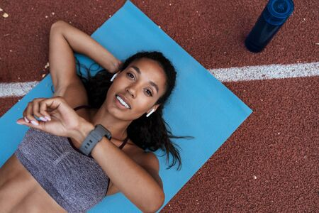 Image of athletic african american woman in sportswear with earpods looking at wristwatch on mat outdoors