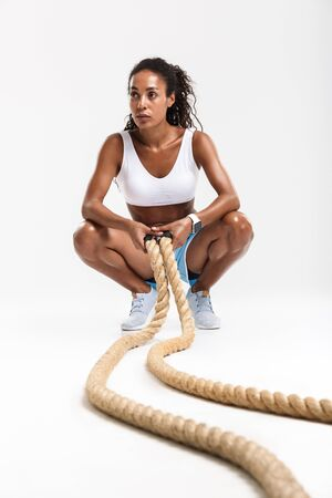 Portrait of serious african american woman squatting while doing exercises with batting ropes isolated over white background