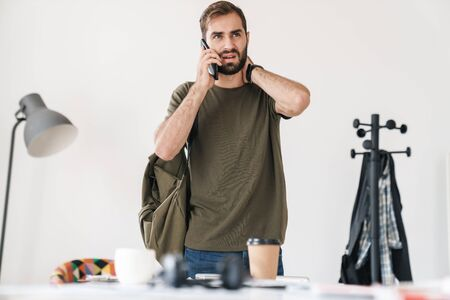 Image of handsome perplexed man with bag talking on cellphone and touching his neck while working in bright office Imagens