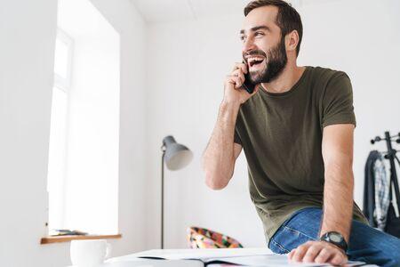 Image d'un bel homme riant parlant au téléphone portable et lisant des documents assis sur un bureau dans un bureau lumineux Banque d'images