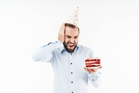 Image of irritated party man screaming and grabbing his head while holding birthday cake isolated over white background Reklamní fotografie