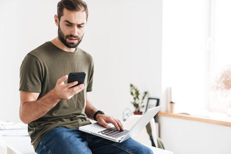 Image of handsome confused man typing on cellphone and using laptop while sitting on desk in bright office
