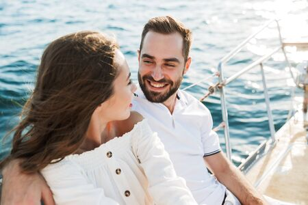 Image of a positive optimistic happy young loving couple outdoors on yacht in sea hugging. Stock Photo
