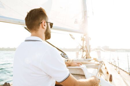 Image of a concentrated handsome young amazing man outdoors on yacht in sea. Reklamní fotografie - 137896056