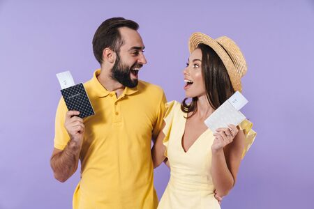 Happy excited beautiful young couple wearing casual clothing standing isolated over violet background, showing passport with flight tickets Stockfoto