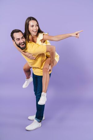 Happy excited beautiful young couple wearing casual clothing standing isolated over violet background, piggyback ride, pointing finger away