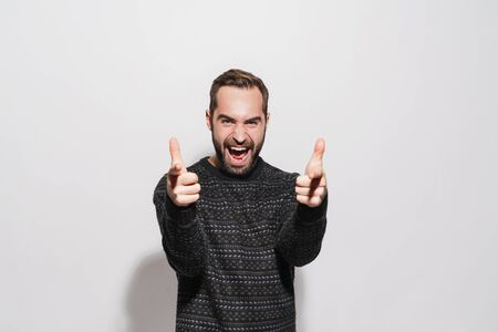 Image of unshaven brunette man in winter sweater screaming and pointing finger at camera isolated over gray background