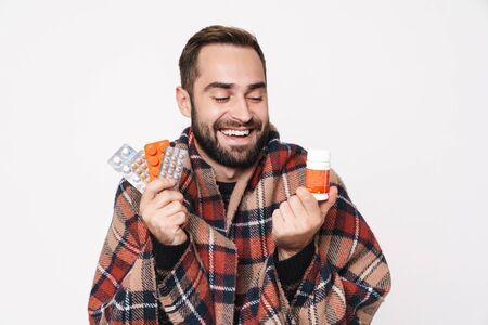 Portrait of happy caucasian guy wrapped in blanket holding bunch of tablets due to flu isolated over white background