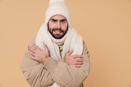 Image of displeased young man in winter clothes shaking and trembling from cold isolated over beige background