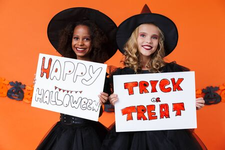 Image of smiling multinational girls in black halloween costumes holding placards isolated over orange pumpkin wall Stock Photo