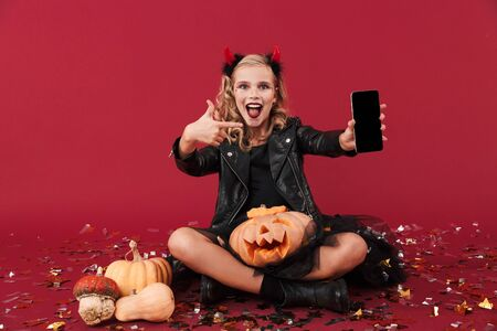 Picture of smiling little girl devil in carnival halloween costume isolated over red wall background holding pumpkin showing empty display of mobile phone. Zdjęcie Seryjne