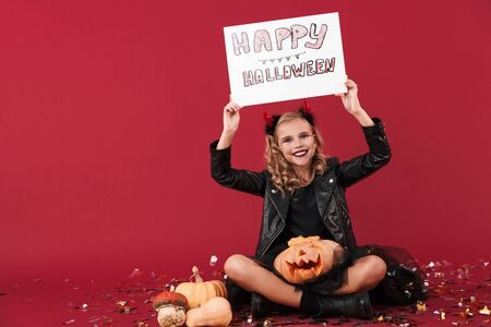 Picture of cheery pleased little girl devil in carnival halloween costume isolated over red wall background holding pumpkin and copyspace blank with halloween text. Zdjęcie Seryjne