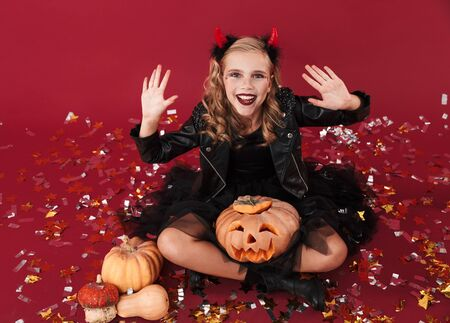 Picture of cheerful pleased little girl devil in carnival halloween costume isolated over red wall background holding pumpkin.
