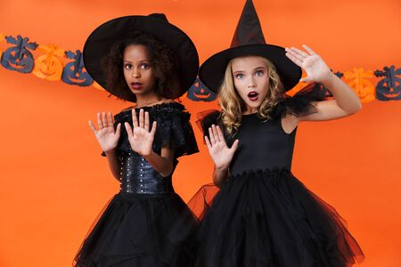 Image of frightened witch girls in black halloween costumes looking at camera and showing stop gesture isolated over orange pumpkin wall