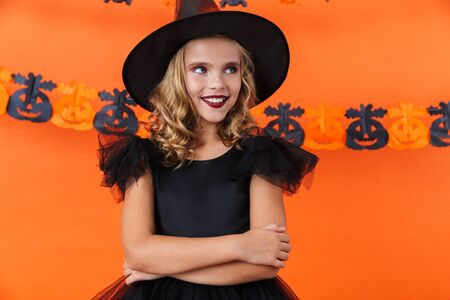 Image of joyful caucasian girl in black halloween costume smiling and looking aside isolated over orange pumpkin wall