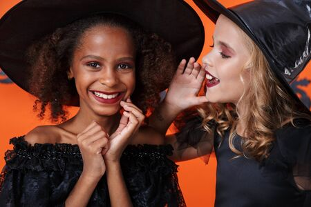 Image of pleased girl in black halloween costume whispering secret to friend in her ear isolated over orange pumpkin wall