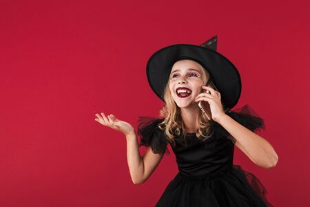 Image of happy smiling little girl witch in carnival halloween costume isolated over red wall background talking by mobile phone. Zdjęcie Seryjne