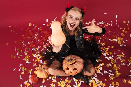 Picture of optimistic little girl devil in carnival halloween costume isolated over red wall background holding pumpkin pointing. Zdjęcie Seryjne