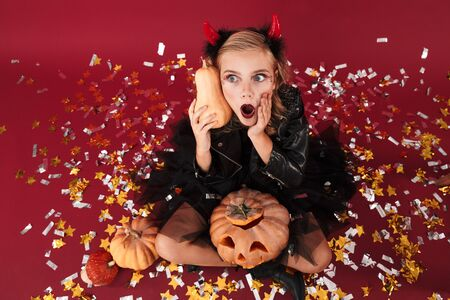 Picture of shocked little girl devil in carnival halloween costume isolated over red wall background holding pumpkin as mobile phone talking.