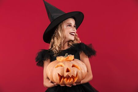 Cheerful little girl wearing Halloween witch costume standing isolated over red background, holding carved pumpkin