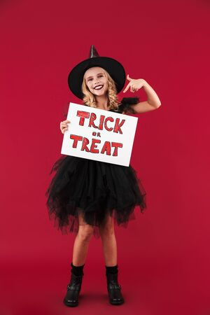 Photo of cheery positive little girl witch in carnival halloween costume isolated over red wall background holding copyspace blank with trick or treat text.