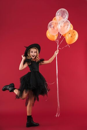 Image of positive happy pretty little girl witch in carnival halloween costume holding balloons isolated over red wall background.