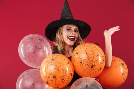 Cheerful little girl wearing Halloween witch costume standing isolated over red background, holding bunch of balloons