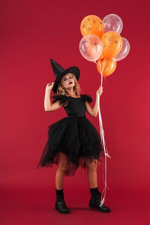 Image of serious pretty little girl witch in carnival halloween costume holding balloons isolated over red wall background.