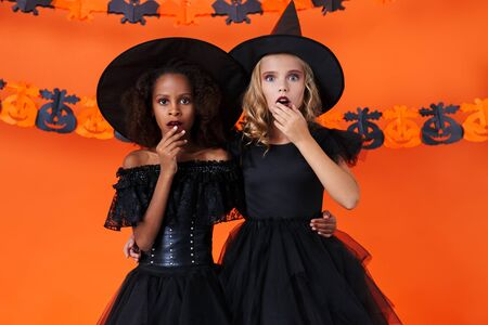 Image of surprised multinational girls in black halloween costumes hugging and looking at camera isolated over orange pumpkin wall